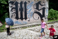 FILE - a family walks by a wall covered by a symbol from the Mara Salvatrucha, of MS-13 gang in Ilopango, El Salvador.