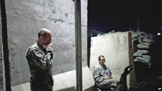 Soldiers from the US Army's 10th Combat Aviation Brigade take a break in a designated smoking area at Jalalabad Air Field in Nangarhar province, Afghanistan, May 3, 2011
