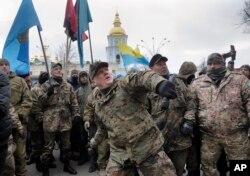 FILE - Mykola Kokhanivsky, commander of a volunteer battalion, throws a stone against the window of an office that belongs to Ukraine tycoon Rinat Akhmetov in Kyiv, Feb. 20, 2016.