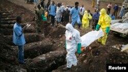 Les agents de santé portent le corps d'une victime Ebola pour l'enterrement dans un cimetière de Freetown, le 17 Décembre 2014.