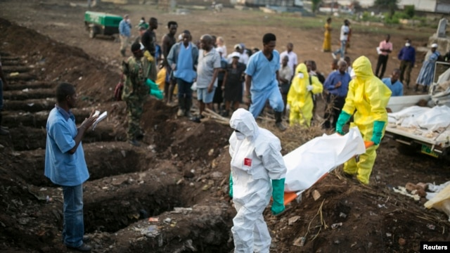 FILE - Health workers carry the body of an Ebola victim for burial Dec. 17, 2014, at a cemetery in Freetown.