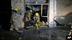 Afghan firefighters spray water at the site of a suicide attack targeting parliamentarian Gul Pacha Mujedi in Kabul, Afghanistan, March 29, 2015.