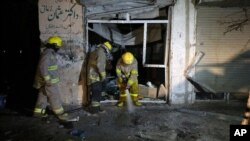Petugas pemadam kebakaran Afghanistan menyemprotkan air ke lokasi ledakan bom bunuh diri di Kabul, Minggu (29/3).