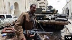 Một binh sĩ của phe nổi dậy Libya bên cạnh chiếc xe tăng chiếm được của lực lượng Gadhafi ở Misrata, ngày 24/4/2011