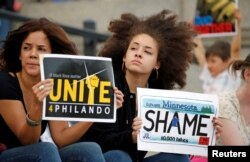 Two woman hold protest signs in support of Philando Castile during a rally on the capitol steps after a jury found St. Anthony Police Department officer Jeronimo Yanez not guilty of second-degree manslaughter in the death of Castile, in St. Paul, Minnesota.