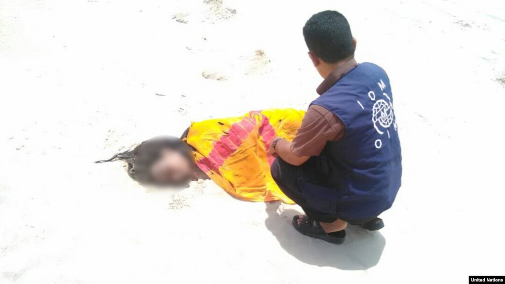 UN Migration Agency staff tend to the remains of a deceased migrant on a beach in Yemen.