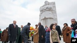 Homeland Security Secretary Jeh Johnson, left, participates in a wreath laying ceremony at the Martin Luther King, Jr. Memorial, on MLK Day, Monday, Jan. 19, 2015, in Washington. Also attending were DC Mayor Muriel Bowser, center, with Harry Johnson, Pre