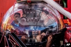Seychelles President Danny Faure, left, sits inside a submersible on the deck of vessel Ocean Zephyr, off the coast of Desroches, in the outer islands of Seychelles, April 13, 2019.