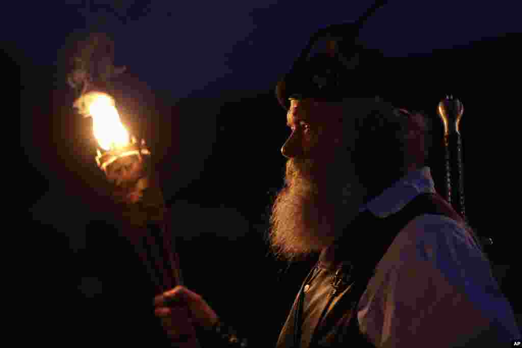 Al Thompson, of Milan, Ind., waits to announce his clan's arrival during the opening torchlight service of the 64th annual Grandfather Mountain Highland Games at MacRae Meadows in Linville, N.C., July 11, 2019. The games celebrate the history and culture of Scottish people in North Carolina.