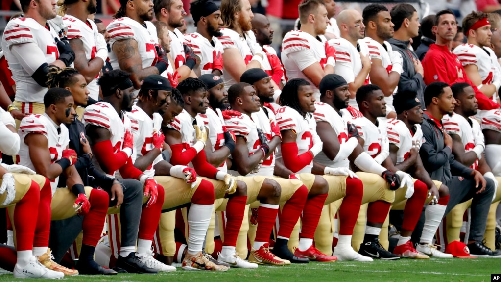 Members of the San Francisco 49ers kneel during the national anthem as others stand during the first half of an NFL football game against the Arizona Cardinals, Oct. 1, 2017, in Glendale, Arizona.