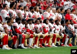 FILE - Members of the San Francisco 49ers kneel during the national anthem as others stand during the first half of an NFL football game against the Arizona Cardinals, Oct. 1, 2017, in Glendale, Arizona.