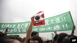 Residents of Dalian demand the removal of a local petrochemical plant at a protest in the city August 14, 2011