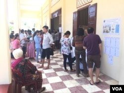 Voters look for names and line up to vote at a polling station at Wat Niroth temple in Niroth commune of Phnom Penh's Chbar Ampov district. (Hul Reaksmey/VOA Khmer)
