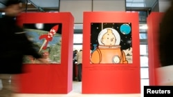 Visitors pass by drawings by Belgium illustrator Herge during a Tintin exhibition in Paris, Dec.19, 2006. The country enters the space race, as illustrated in the comic strip in the 1950s, with plans to form a space agency next year.
