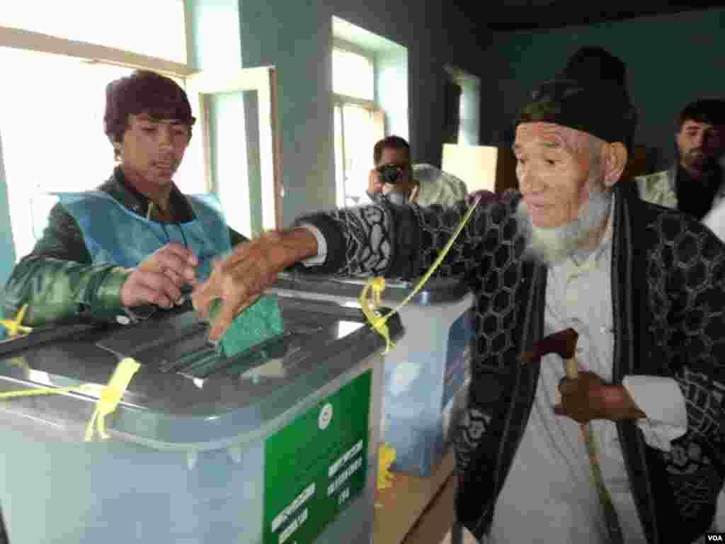 مرد سالمندی در حال انداختن رأی به صندوق - ۵ آوریل ۲۰۱۴
