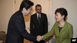 지난 3월 네덜란드 헤이그에서 열린 미-한-일 3국 정상회담에 앞서 박근혜 한국 대통령(왼쪽)과 아베 신조 일본 총리가 악수하고 있다. 바락 오바마 미국 대통령(가운데)이 이를 지켜보고 있다. (자료사진)
