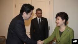 2014년 3월 25일 네덜란드 헤이그에서 미-한-일 3국 정상회담에 앞서 박근혜 한국 대통령(왼쪽)과 아베 신조 일본 총리가 악수하고 있는 가운데, 바락 오바마 미국 대통령이 이를 지켜보고 있다.