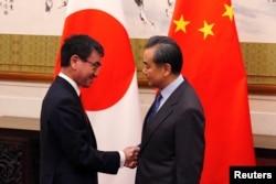 28일 중국을 방문한 고노 다로 일본 외무상(왼쪽)이 베이징 영빈관에서 왕이 중국 외교부장과 만나 악수하고 있다.