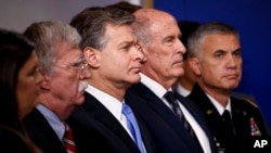 From left, White House press secretary Sarah Sanders, national security adviser John Bolton, FBI Director Christopher Wray, Director of National Intelligence Dan Coats and National Security Agency Director Gen. Paul Nakasone listen during the daily press briefing at the White House, Aug. 2, 2018.