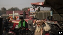 Sonu Singh ties his turban while getting ready to join other farmers protesting against new farming laws they say will result in exploitation by corporations.