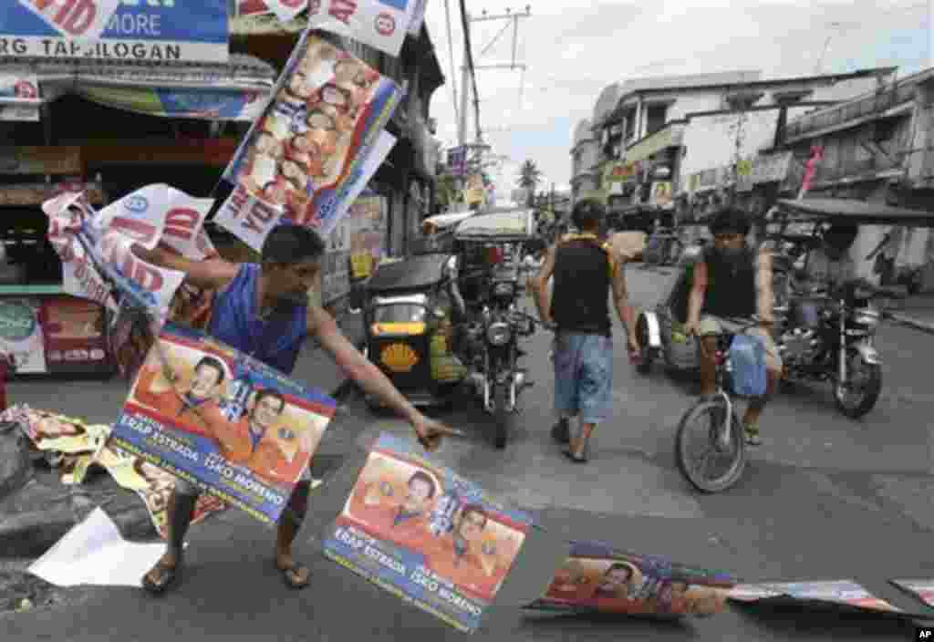 필리핀 총선 다음날인 14일 마닐라 시내에 걸려있는 총선 후보자 홍보물을 치우는 시민.