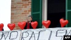 """Une femme sur son balcon où elle a mis des ballons rouges portant le nom des victimes et une banderole disant """"non au racisme"""" lors d'une manifestation antiraciste dans la ville de Macerata, en Italie, le 10 février 2018."""