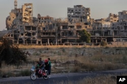 FILE - People ride their motorcycle by damaged buildings in the old town of Homs, Syria, Aug. 15, 2018. Turkish President Recep Tayyip Erdogan earlier this month unveiled plans for major housing projects in a proposed Turkish-controlled military security zone in Syria.