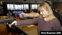 FILE - Clark Aposhian demonstrates with a plastic gun, rear, while Joanna Baginska, a fourth-grade teacher from Odyssey Charter School, in American Fork, Utah, aims a handgun during concealed-weapons training training.