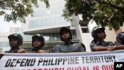 Policemen stand guard behind a protest banner outside the Chinese consulate in Manila's financial district of Makati, Philippines, May 11, 2012.
