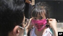 FILE - In this June 10, 2020, file photo, Olivia Chan's father helps her with a new mask she received during a graduation ceremony for her Pre-K class in front of Bradford School in Jersey City, N.J. (AP Photo/Seth Wenig, File)
