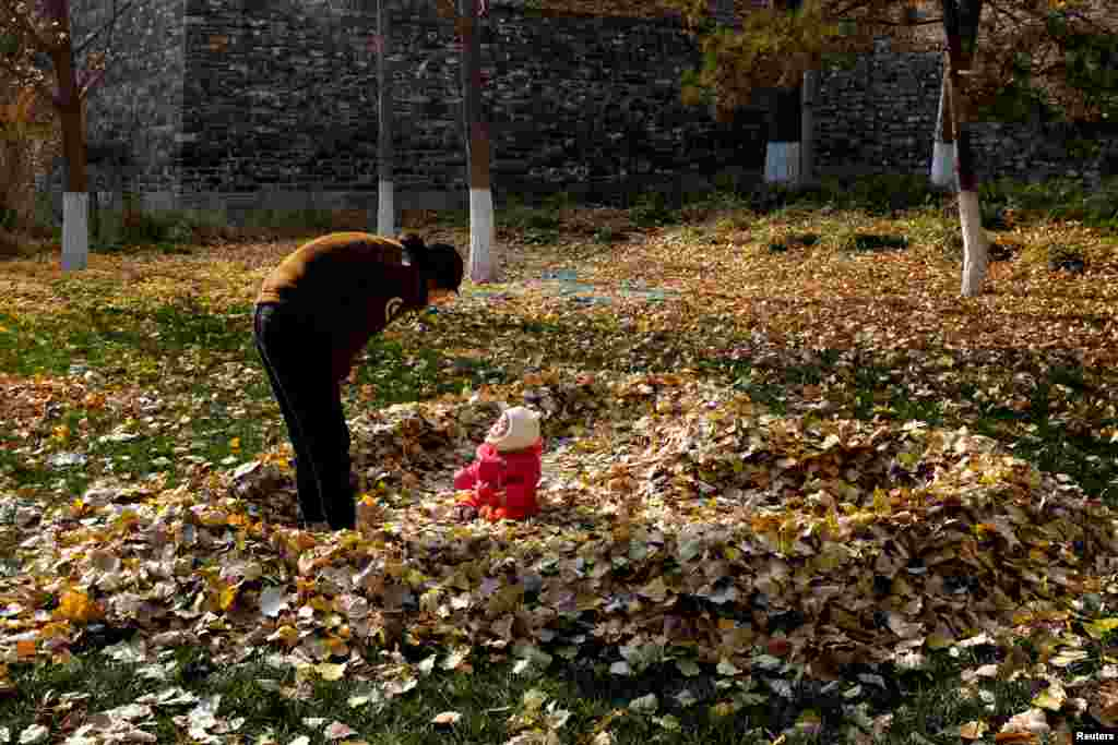 A mother looks at her daughter sitting in a pile of fallen leaves shaped like a heart, in Beijing, China, Nov. 19, 2018.