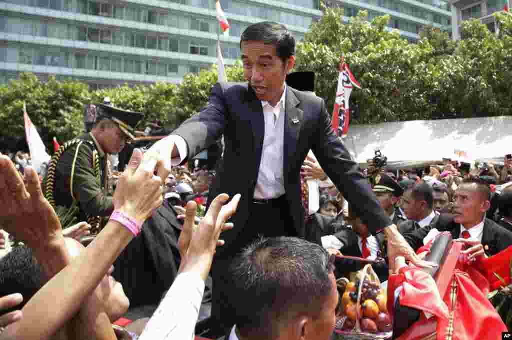 PresidenJoko Widodo di tengah kerumunan rakyat dalam parade jalanan menyusul pelantikannya di Jakarta (20/10).(AP/Achmad Ibrahim)