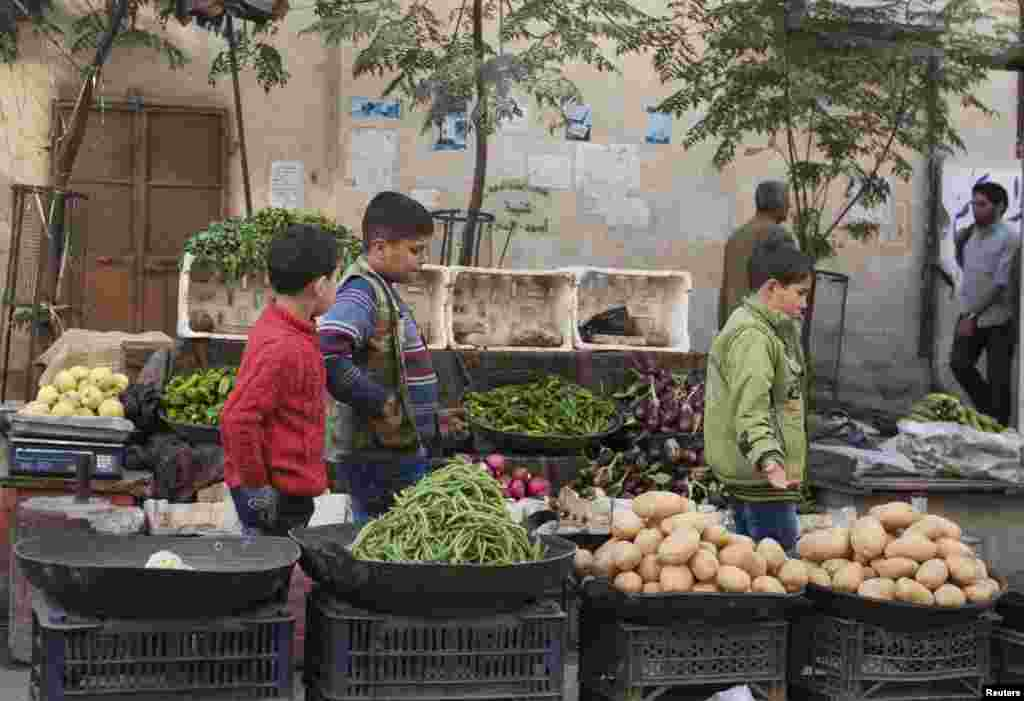 Boys pass by a vegetable stall in Aleppo, Oct. 21, 2013.