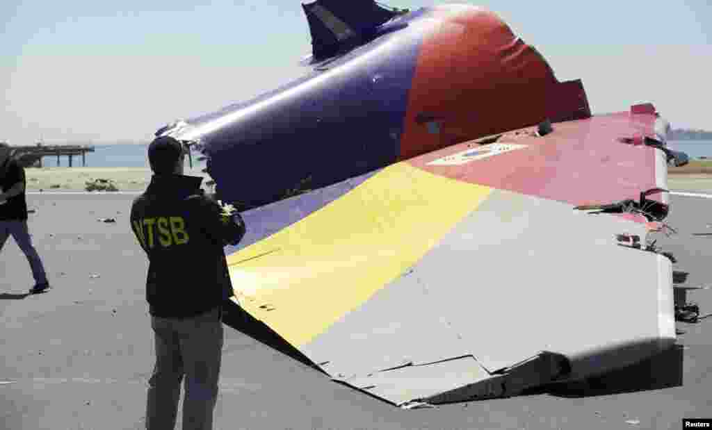 A National Transportation Safety Board (NTSB) investigator looks at the tail section of the Asiana Airlines Flight 214 that crashed at San Francisco International Airport, July 7, 2013. (NTSB)