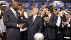 Alonzo Mourning, kiri, bersalaman dengan pemilik Miami Heat Micky Arison, sementara pelatih Erik Spoelstra tersenyum setelah Heat mengalahkan Chicago Bulls 83-80 di game 5 final Wilayah Timur NBA Kamis (26/5) di Chicago.