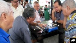Elderly men play board games in Singapore.