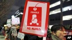 Des manifestants brandissent des pancartes lors d'un rassemblement anti-nucléaire près du bureau du Premier ministre à Tokyo, le 11 mars 2016.
