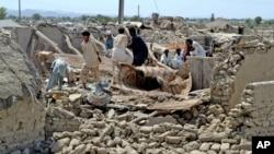 25일 파키스탄 발루치스탄주 아와란 주민들이 지진으로 무너진 집에서 자신들의 물건을 찾고있다.