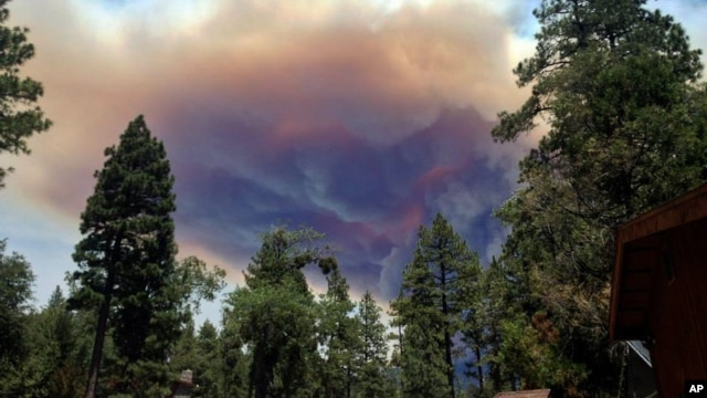 This July 17, 2013, image provided by Meagan Greene shows wildfire smoke near Idyllwild, California. The blaze about 100 miles east of Los Angeles had grown to more than 35 square miles in size and had destroyed several homes.