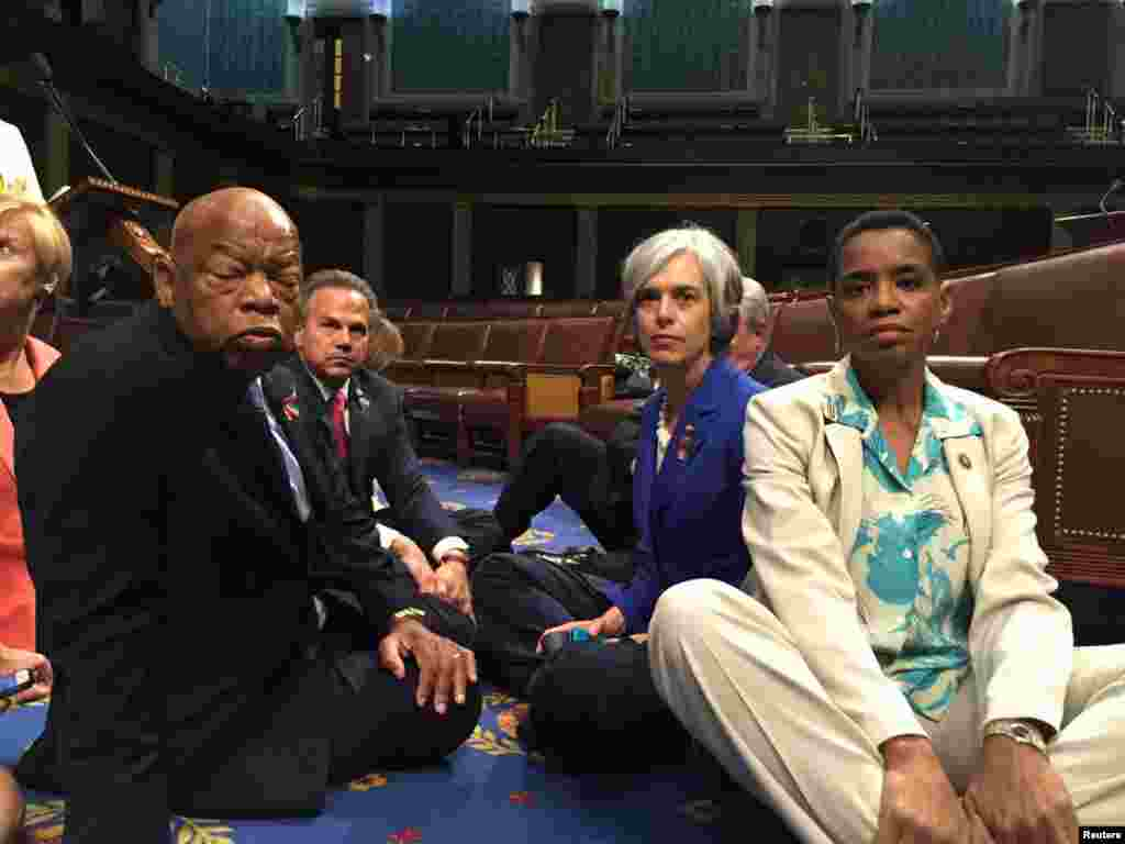 "A photo tweeted from the floor of the U.S. House by Rep. Donna Edwards (R) shows Democratic members of the U.S. House of Representatives, including herself and Rep. John Lewis (L) staging a sit-in on the House floor ""to demand action on common sense gun legislation"" on Capitol Hill in Washington."