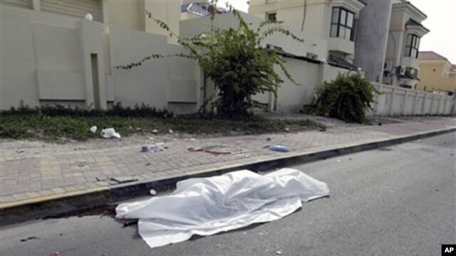 The body of a person killed during clashes between demonstrators and police lies in the street in Manama, on Feb 17 2011
