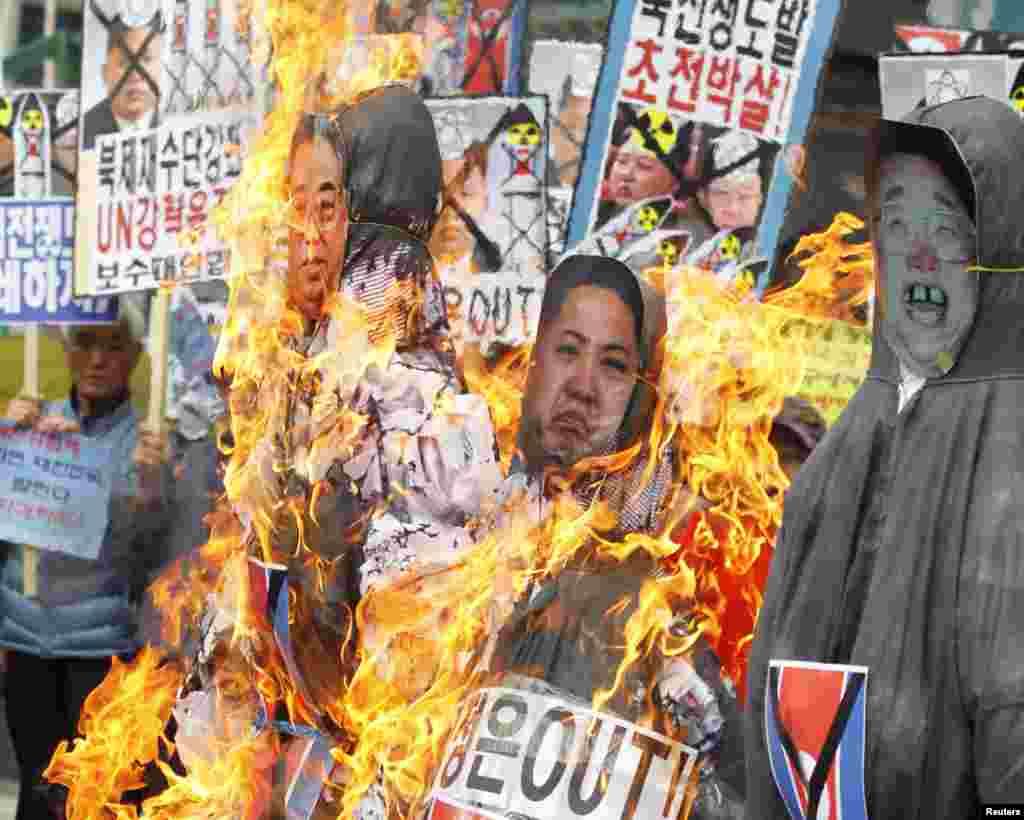 Người Nam Triều Tiên đốt hình nộm của lãnh tụ Kim Jong-un, người cha Kim Jong-il và ông nội Kim Il-sung trong khi biểu tình ở trung tâm Seoul.