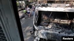 Orang melewati kendaraan yang dibakar di tempat bentrokan antara pemrotes dan polisi di Bangkok, Thailand, 7 Desember 2013.