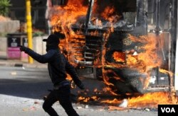 A protesting student runs past a burning bus off campus outside the University of the Witwatersrand in Johannesburg, South Africa on Monday, Oct. 10, 2016. (AP Photo)