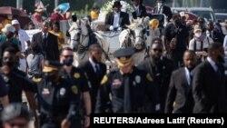 Para petugas kepolisian berbaris di depan kereta kuda yang membawa peti jenazah George Floyd sebelum pemakaman di Pearland, Texas, 9 Juni 2020. Kematian Floyd, warga Afrika-Amerika, saat ditahan polisi memicu gerakan menentang rasisme di seluruh dunia.