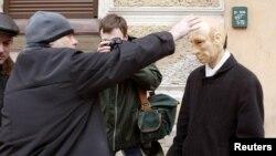 Seorang polisi berpakaian sipil Rusia berusaha melepas topeng yang menampilkan Presiden Vladimir Putin dari seorang demonstran di pusat kota St. Petersburg, 28 Februari 2004. (REUTERS/Alexander Demianchuk)