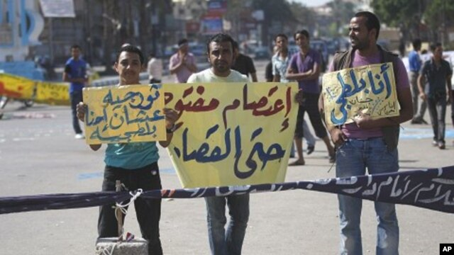 Demonstrators hold banners as they protest in the Martyrs Square in Suez, Egypt, as hundreds of Egyptians attacked a courtroom in Cairo, July 5, 2011