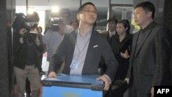 Сотрудник южнокорейской полиции с конфискованным оборудованием Google Incorporated