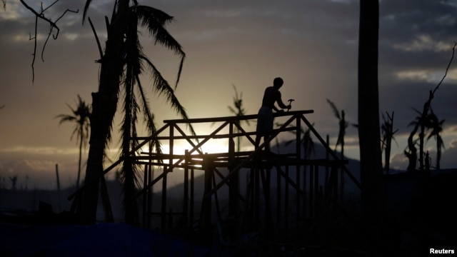 A man is silhouetted as he builds a wooden house in an area destroyed by Typhoon Haiyan, in Palo November 19, 2013.