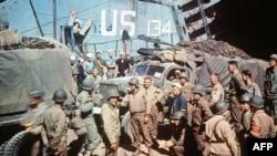 រូបឯកសារ៖ ទាហានអាមេរិកប្រមូលផ្ដុំគ្នានៅជុំវិញឡានដែលទើបដាក់ចេញពីនាវាបន្ទាប់ពីថ្ងៃ D-Day នៅថ្ងៃទី៦ មិថុនា ១៩៤៤ ក្រោយពេលកម្លាំងរបស់សម្ព័ន្ធមិត្តបានវាយប្រហារនៅឆ្នេរ Normandy ។